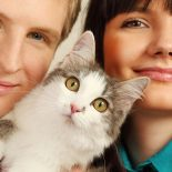 Smiling young husband and wife hold surprised cat; focus on cat